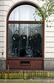 Four priests stand in an office window to watch the Pope's Mass in Warsaw.